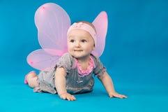 服装的女孩在蓝色背景的一只蝴蝶 库存照片
