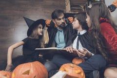 服装的孩子为万圣夜坐地板在拿着一本书的一个黑斗篷的一个人附近 库存图片