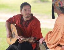 服装的新生公平的年轻人演奏弦乐器 免版税库存图片