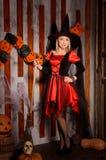 服装的年轻可爱的巫婆有笤帚的 免版税图库摄影