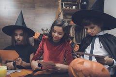 服装神仙的妖怪的三个孩子万圣夜党的删去了从纸的棒 免版税库存照片