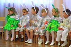服装野兔的孩子坐午后的演出在幼儿园新年 免版税图库摄影