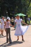 晴朗的夏日在城市公园 跳舞与游人人民的女孩公开艺人在军事黄铜的音乐下 免版税库存照片