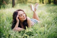 晴朗的夏日,说谎在草的一个美丽的少妇 免版税图库摄影
