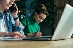 晴朗的日 一起坐在办公室的两个年轻女商人在桌和工作上 在桌膝上型计算机和纸图 免版税库存图片