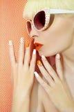 晴朗的橙色修指甲和构成 库存图片