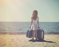 晴朗的海滩的葡萄酒孩子带着旅行手提箱 免版税图库摄影
