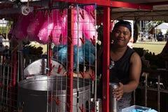 朗芒芽地,菲律宾- 2018年7月27日:市场立场的桃红色棉花糖卖主 卖甜点的微笑的菲律宾人 库存照片