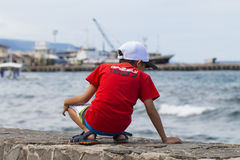 朗芒芽地,菲律宾- 2017年5月13日:红色T恤杉的一个男孩看海和口岸 特写镜头红色绳索海上旅行 免版税图库摄影