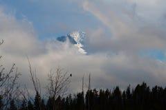 渴望与雪和云彩的峰顶 库存照片