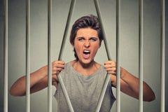 绝望恼怒的她的监狱牢房妇女弯曲的酒吧  库存照片