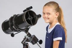 望远镜的年轻天文学家是微笑和看对框架 免版税库存照片