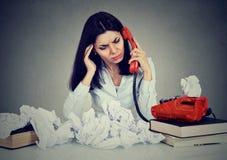 绝望雇员,妇女谈话在一个电话在她的办公室 免版税库存图片