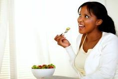 朝右边看和吃一道蔬菜沙拉的夫人 库存图片
