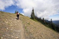 朝向山道路的女性远足者 免版税图库摄影