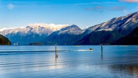 朝向有金黄耳朵、兴奋峰顶和其他峰顶的峰顶的Pitt湖的渔船在海岸山 库存图片