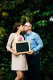 期待拿着一块空白的木炭的怀孕的愉快的时髦的夫妇上 免版税库存图片