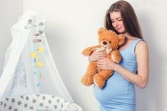 期待有一个棕色逗人喜爱的玩具熊的妇女一个婴孩 免版税库存照片