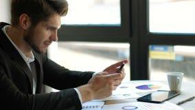 期望的消息 使用他的有微笑的年轻英俊的人智能手机,当坐在他的工作地点时 免版税库存照片