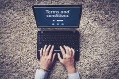 期限和条件在膝上型计算机屏幕 键入在键盘的妇女手 库存图片
