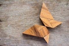 木七巧板难题在蝴蝶形状背景中 库存图片