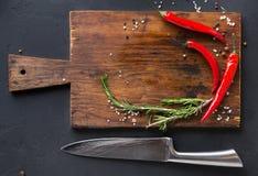 木书桌用香料和辣椒在黑暗的背景 库存图片