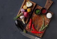 木书桌用香料和辣椒,在一个箱子的不同的烹调成份在黑暗的背景 免版税图库摄影