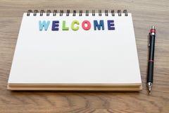 木五颜六色的信件词欢迎放下在木头后面上的笔记本 免版税库存照片