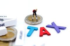 木五颜六色的文本是与站立在硬币的旅客的税和块2018年 税演算的图象用途每年的大家 库存照片
