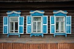 木传统俄国房子墙壁有窗口的和被雕刻的框架和样式 图库摄影