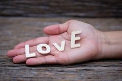 木信件词& x22; LOVE& x22;在woman& x27; s手, 免版税图库摄影
