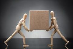 木假的夫妇运载的纸板箱 免版税库存图片
