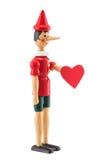 木偶奇遇记与在白色隔绝的心脏的玩具雕象 免版税库存照片
