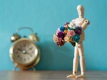 木偶拿着花在金葡萄酒闹钟前面的一朵花在木桌上 背景是蓝色和拷贝空间fo 库存照片
