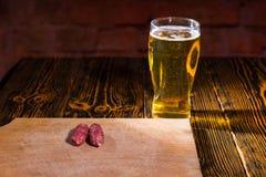 木切板用在充分的杯的香肠啤酒附近 库存照片