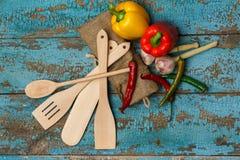木利器和不同的菜在破旧的蓝色backgroun 免版税库存图片