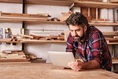 木制品工匠在他的使用一种数字式片剂的演播室 免版税库存照片