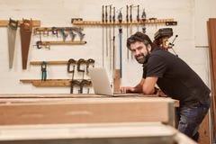 木制品工匠在他的有膝上型计算机的车间演播室 免版税库存照片