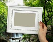 木制框架在背景天然泉瀑布的妇女手上 库存照片