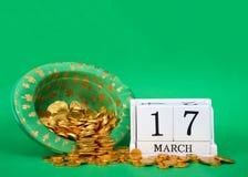 木刻与日期与倾吐在帽子,圣帕特里克` s天外面的金子的3月17日 免版税库存照片