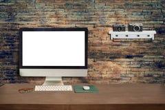木办公桌和空白的显示器与老砖墙 免版税库存图片