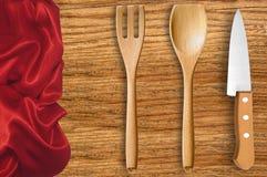 木匙子、叉子和刀子在切板有红色布料的 免版税库存图片