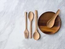 木匙子、叉子和板材在白色大理石 免版税库存图片