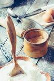 木匙子到陶瓷碗用面粉、银行与Adyghe盐,鸡蛋、滚针、金属筛子和杓子 免版税库存图片
