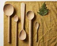 木匙子和一片叶子在餐巾 库存照片