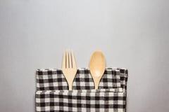 木匙子和叉子与棕色桌镶边了织品 免版税图库摄影