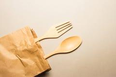 木匙子和叉子在包装纸请求 库存照片