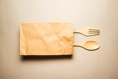 木匙子和叉子在包装纸请求 图库摄影