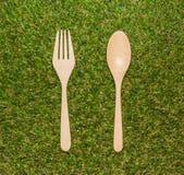 木匙子和叉子在绿草背景 免版税图库摄影