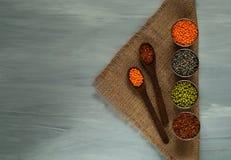 木匙子和各种各样的谷物在金属杯子在粗麻布,健康吃的概念 顶视图 土气的背景 免版税库存图片